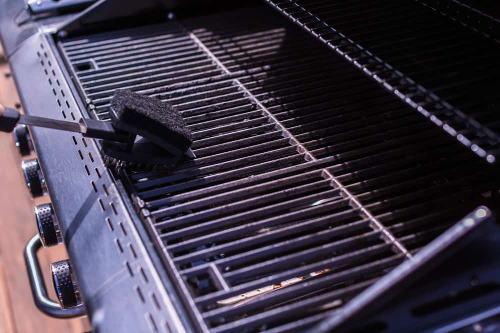 Using a brush to clean a BBQ grill