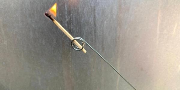 Match holder for manually starting a gas grill with a match